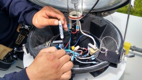 A tower climber services a xenon obstruction light