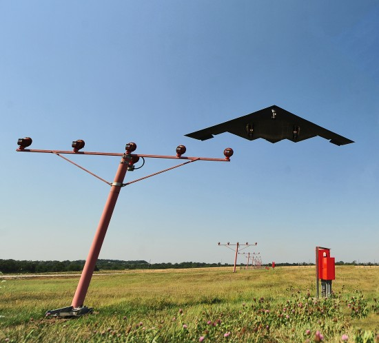 A stealth bomber flies over airport approach lights at Whiteman AFB
