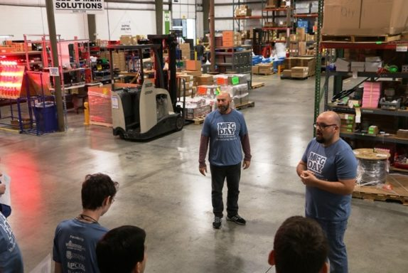 Operations director, Marc, and production supervisor, Jacob, introduce students to the production warehouse on Manufacturing Day.