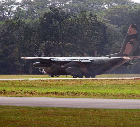 A C-130 on a shirt field with taxiway lights