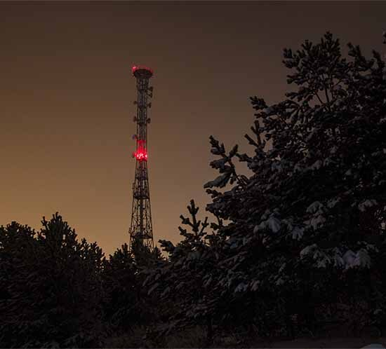 Communications structure with red tower light at night